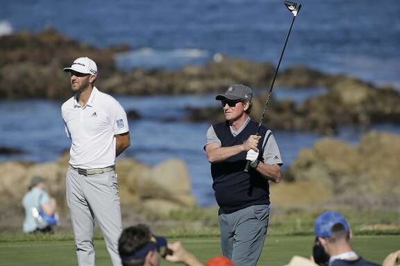 Wayne Gretzky, right, follows his drive as Dustin Johnson, left, looks on from the 13th tee of the Monterey Peninsula Country Club Shore Course during the second round of the AT&T Pebble Beach National Pro-Am golf tournament Friday, Feb. 9, 2018, in Pebble Beach, Calif. (AP Photo/Eric Risberg)
