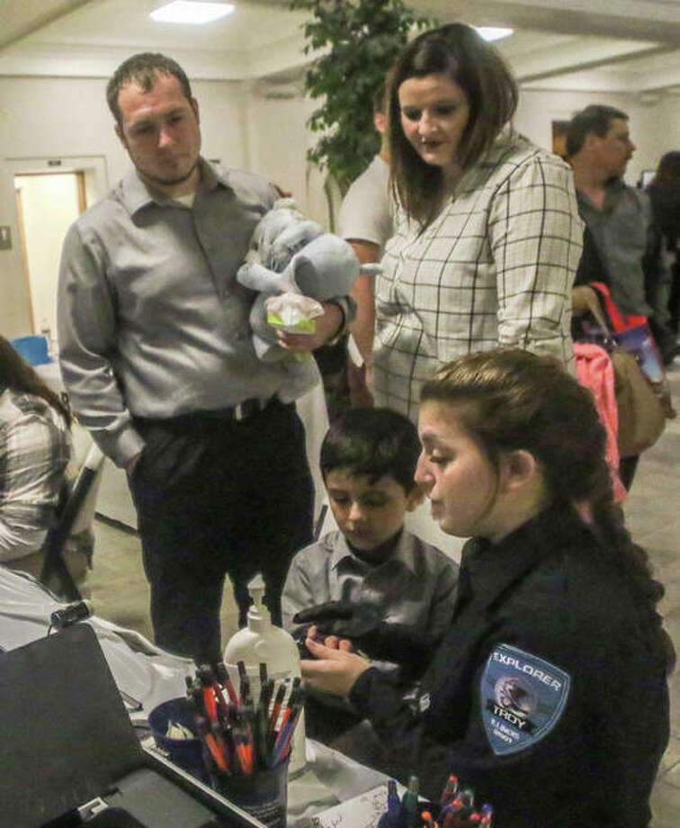 Ryder Marsh is fingerprinted by a police officer with the Explorer Project, based in Troy, Saturday during the National Day of Adoption even held at the Madison County Courthouse. New father Erek Marsh and his biological mother Brandi Ingrham look on. Photo: Nathan Woodside | For The Telegraph