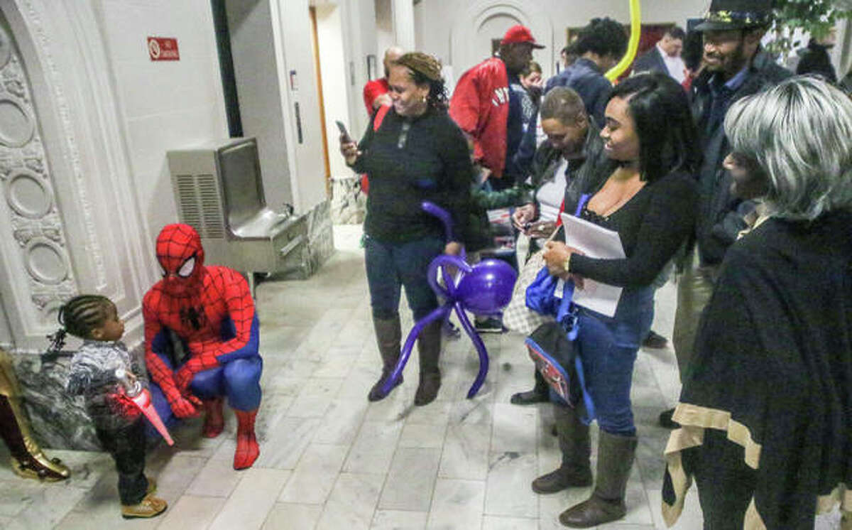 A young girl appears to have a serious conversation with Spiderman Saturday at the Madison County Courthouse during the National Day of Adoption event. There were many activities for the 45 children being officially placed into permanent families, include characters in costume, face painting and a balloon artist.