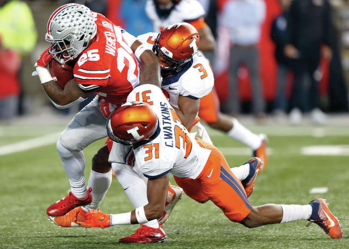 Ohio State running back Mike Weber, left, drags Illinois defenders Del'Shawn Phillips, right, and Cameron Watkins during Saturday's Big Ten game in Columbus, Ohio.