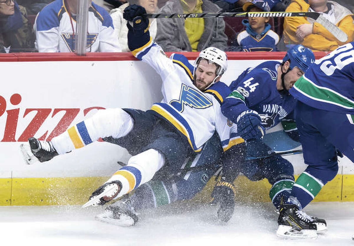 Blues defenseman Joel Edmundson (left) and the Canucks' Erik Gudbranson collide during the third period of a NHL game Saturday night in Vancouver, British Columbia.