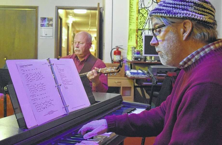Jeff Davidsmeyer plays the piano Thursday night during a Christian music worship circle event at the Christian Performing Arts Productions studio on the west side of Jacksonville's downtown square. In the background is John Potter. Photo: Greg Olson | Journal-Courier