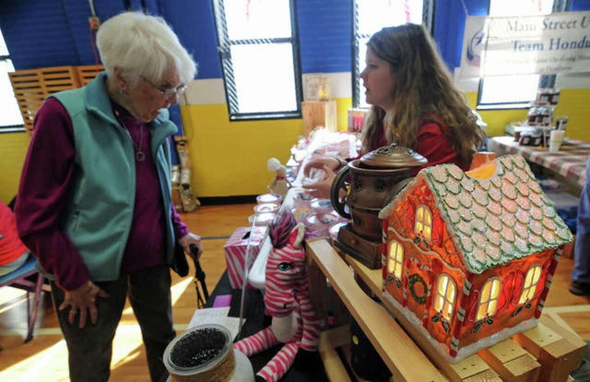 Catherine Sumner of Godfrey examines holiday items offered by Sarah Spone, of Godfrey.