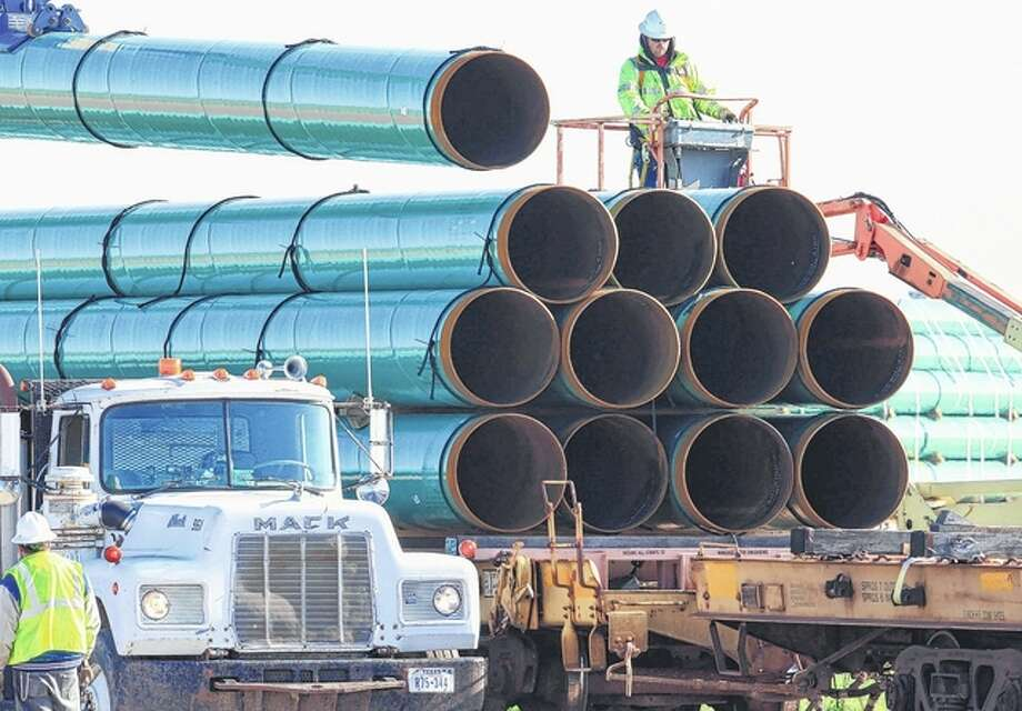 Nati Harnik | AP Workers unload pipes in 2015 for the Dakota Access oil pipeline, which will stretch from the Bakken oil fields in North Dakota to Illinois, including a large part of Morgan County and west-central Illinois. The Dakota Access project, which is mostly completed, has created about 12,000 construction jobs, according to project leader Energy Transfer Partners LP. Most of those jobs are over, however.