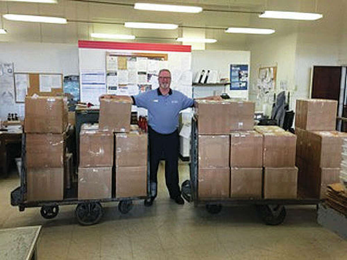 """U.S. Army veteran of 16 years and current U.S. Postal Service representative Mark Bowen stands guard over the Christmas boxes that were ready to ship - and since have been shipped - to current Macoupin County military members serving overseas. The """"Christmas for a Soldier"""" campaign is a joint effort between the Macoupin Military Support Group and Carlinville's Shop Local First organization."""