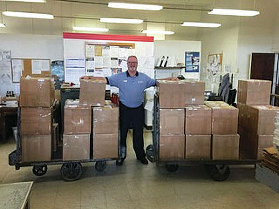 "U.S. Army veteran of 16 years and current U.S. Postal Service representative Mark Bowen stands guard over the Christmas boxes that were ready to ship — and since have been shipped — to current Macoupin County military members serving overseas. The ""Christmas for a Soldier"" campaign is a joint effort between the Macoupin Military Support Group and Carlinville's Shop Local First organization. Photo: For The Telegraph"