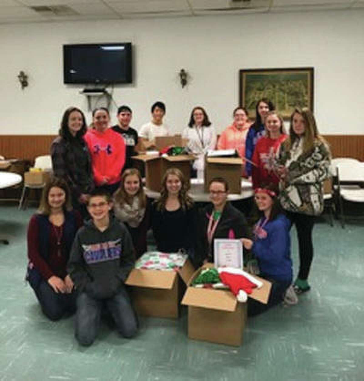 """Student volunteers from Carlinville High School and Carlinville Junior High took a break from sorting and packing """"Christmas for a Soldier"""" donations that were collected by the Macoupin Military Support Group and sent to men and women serving in foreign countries."""