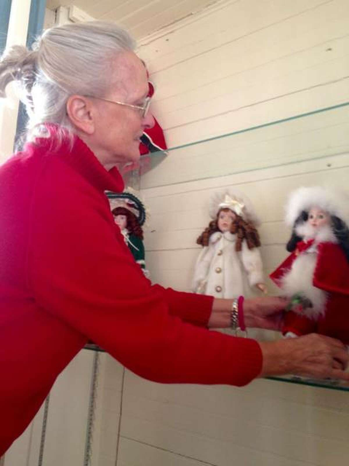 Debbie Schuneman, chairman of the Lucy Haskell Playhouse Association, gently places a doll dressed in fancy attire on a cabinet shelf inside the playhouse while decorating its interior with Victorian Christmas items. Santa will visit the playhouse, 1211 Henry St. in Alton, from noon to 2 p.m. on Dec. 2.