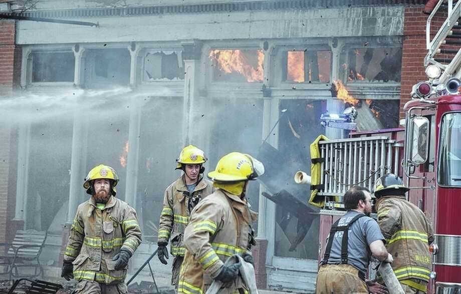 Firefighters from eight departments battle a blaze that destroyed three buildings Tuesday in White Hall. The fire began in a residential building and spread quickly to neighboring buildings. Photo: Samantha McDaniel-Ogletree | Journal-Courier