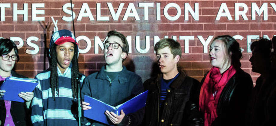 Singers from Marquette High School perform Tuesday evening in front of the Alton Salvation Army during the Alton Corps' Tree Of Lights ceremony. Students from the school's drama club presented this year's Tree of Lights Chairs, Mark and Mary Cousley, with a check of more than $300 raised during a recent performance for the Red Kettle Campaign. The Cousleys announced this year's goal for the Alton-area campaign at $90,000. Last year, the campaign brought in $100,000, beating its $85,000 goal. Photo: Nathan Woodside | For The Telegraph
