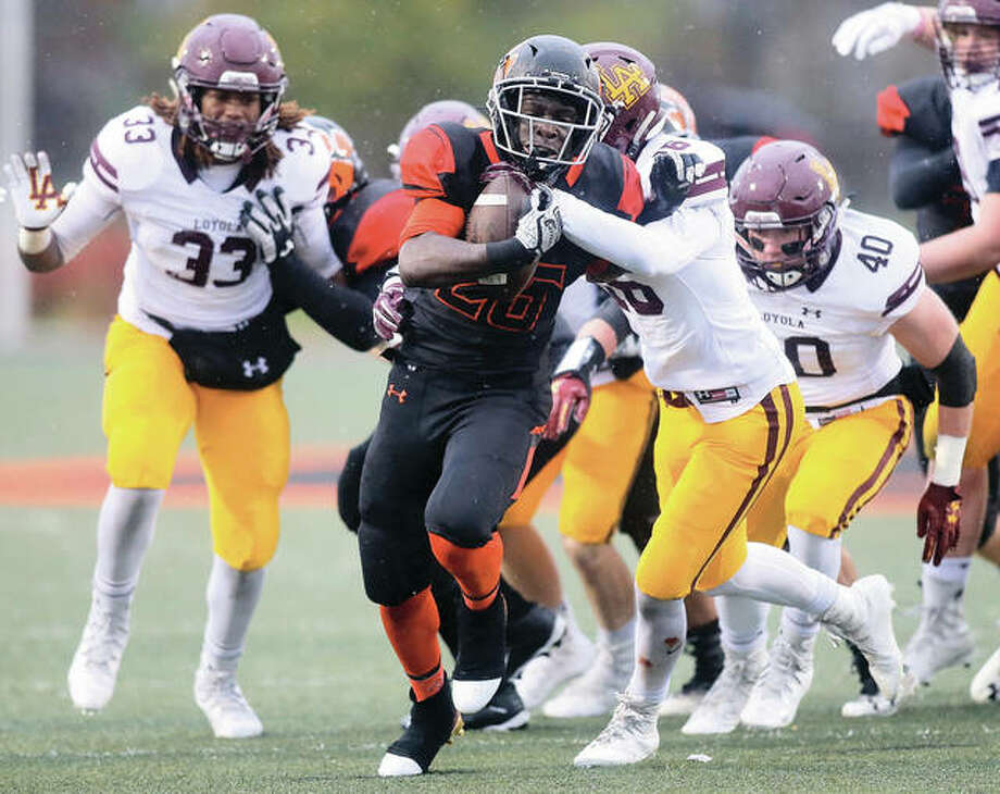 Edwardsville freshman running back Justin Johnson (center) breaks through the line and fends off Loyola free safety Jake Gonzalez (16) during a Class 8A semifinal playoff game on Saturday at the District 7 Sports Complex in Edwardsville. Photo: Scott Kane / For The Telegraph