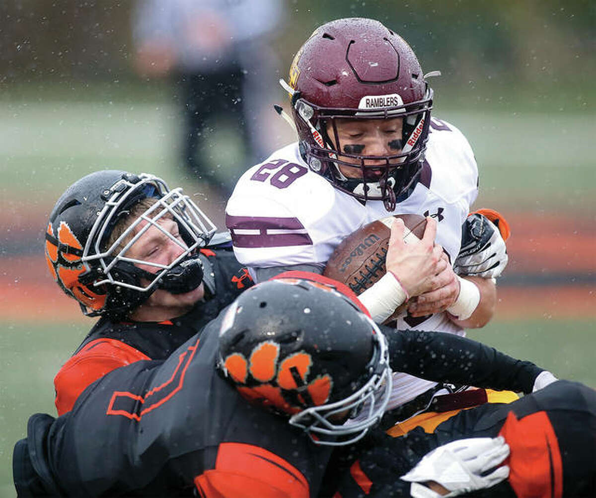 Loyola running back Michael Gavric (28) is stacked up and taken by by Edwardsville defenders during Saturday's the Class 8A state semifinal game in Edwardsville.