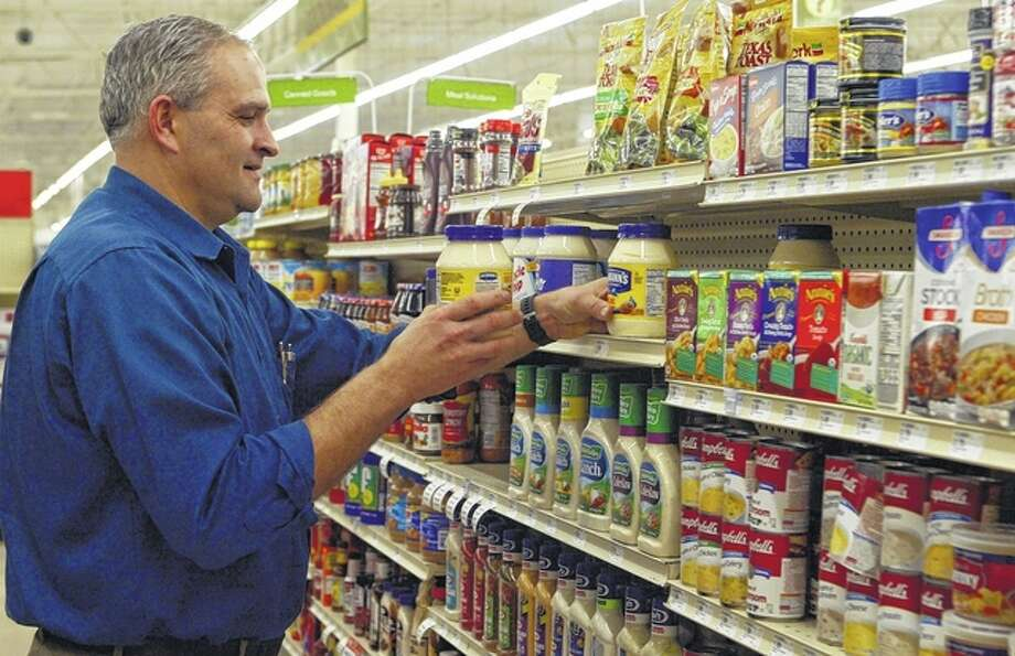 Jacksonville Shopko store manager Steve Wade straightens items on a shelf in the store's new grocery department. Photo: Greg Olson | Journal-Courier