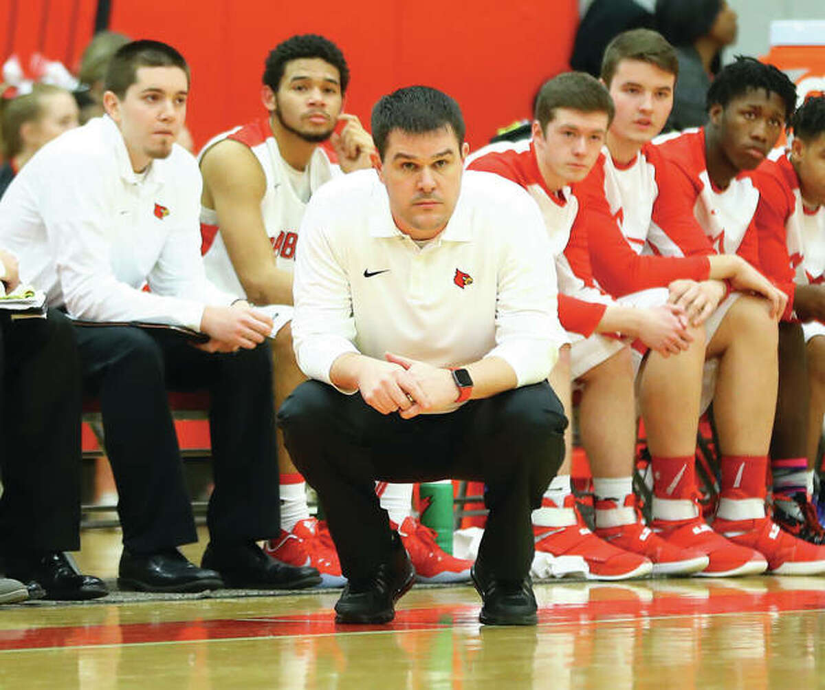Alton coach Eric Smith watches his team from the sideline during a game against Belleville East last season at Alton High. The Redbirds were back at home Wednesday night and improved to 2-0 with a tourney victory over Ritenour.