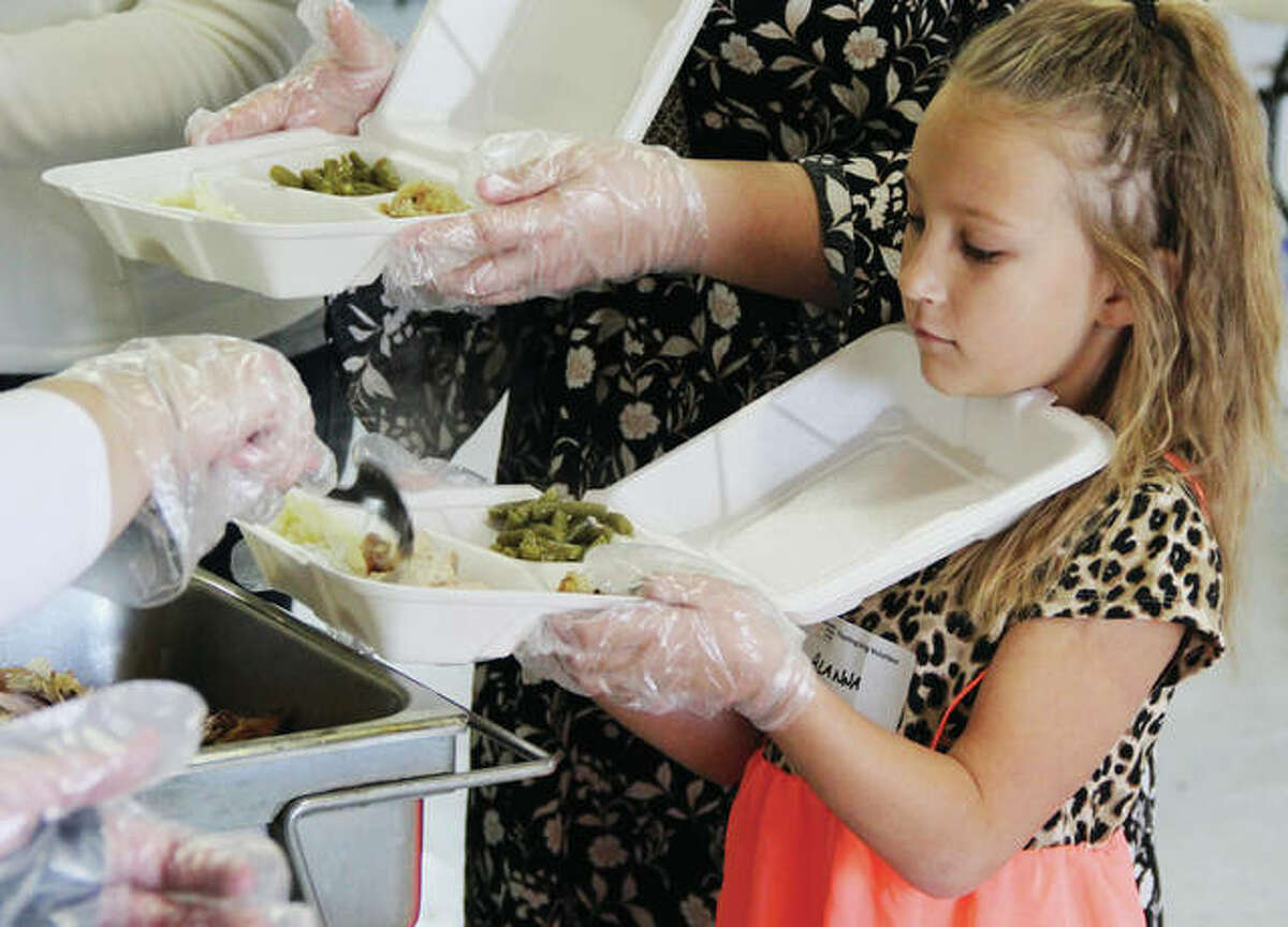 Volunteer Alanna Bennett, 8, of Highland, balances a Thanskgiving dinner at Community Hope Center in Cottage Hills while other volunteers fill her to-go container. Alanna was among volunteers helping prepare Thanskgiving dinner at Community Hope Center in Cottage Hills Thursday morning as part of the centers Thanksgiving dinner for distribution to the elderly and shut-ins, as well as to first responders throughout the area.