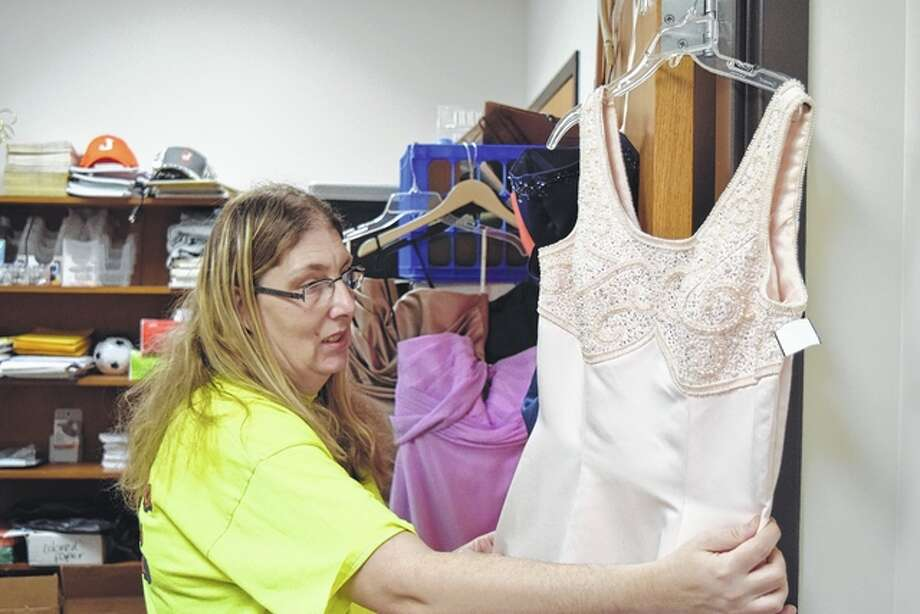 "Amanda Mitchell of Jacksonville, who attends Pathway Services' vocational day program, looks at a prom dress that were donated for Pathway women who plan to attend the ""Night to Shine"" prom in Quincy Friday and/or Pathway's inaugural prom, ""An Enchanted Evening,"" April 1. Photo: Greg Olson 