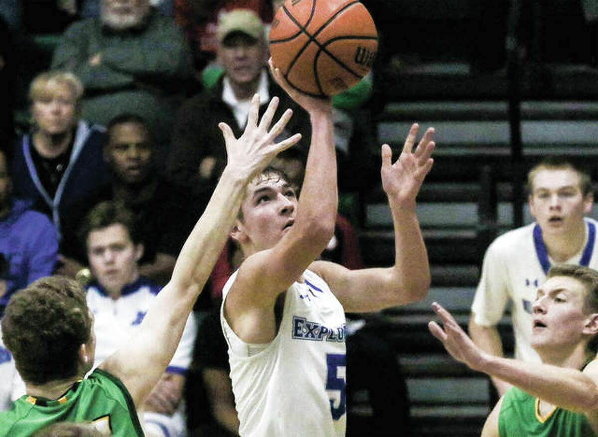 Marquette Catholic's Chris Hartrich (middle) puts up a shot in the lane between a pair of Southwestern defenders Friday night in the Explorers' semifinal victory in the Metro East Thanksgiving Turkey Tip-Off Classic at Hooks Gym in Edwardsville.