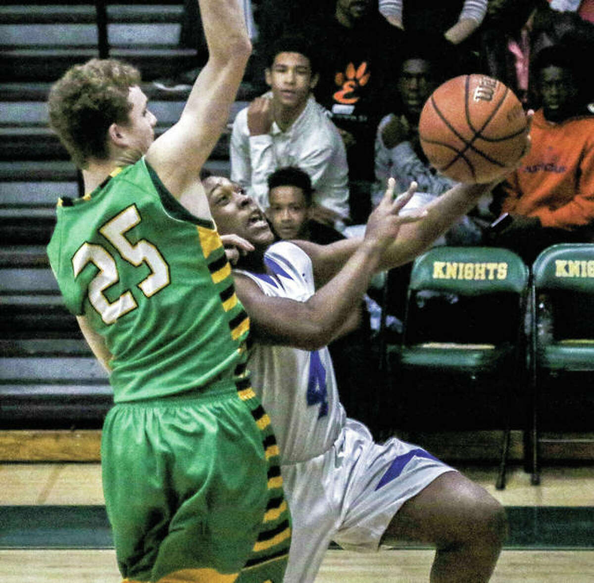 Marquette's Iggy McGee (right) drives to the hoop for a shot contested by Southwestern's Kyler Seyfried in MEL Tourney play Friday night in Edwardsville.
