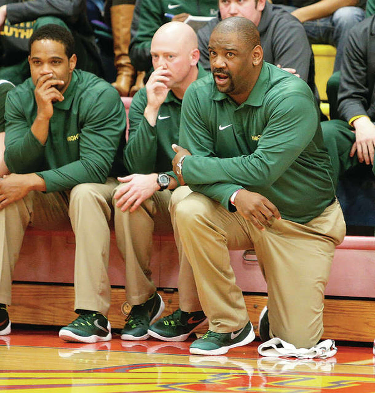 Metro East Lutheran coach Anthony Smith (right), shown kneeling in front of his team's bench during a Knights win at Roxana two seasons ago, has MEL in the championship game against top-seeded Marquette on Saturday night in the 37th annual Metro East Lutheran Thanksgiving Turkey Tip-Off Classic in Edwardsville.