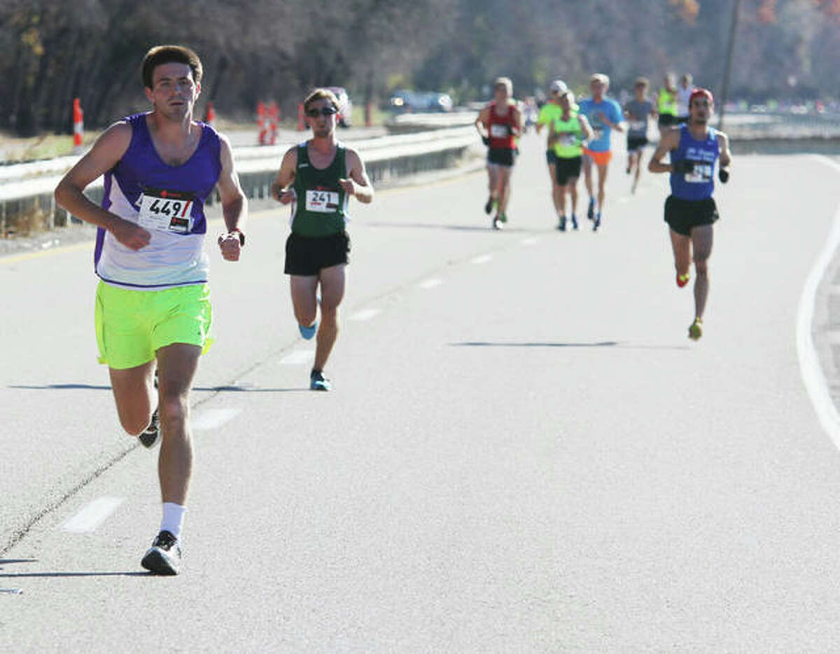 Runner Benjamin Richter, left, of Troy (449) leads the pack early in the 58th annual Great River Road Run along the Great River Road Saturday. Richter completed the run in 56:34, first overall and first in men's 0-39. An estimated 1,000 runners participated in either a 2- or 10-mile run, which is sponsored by the Alton Road Runners Club.