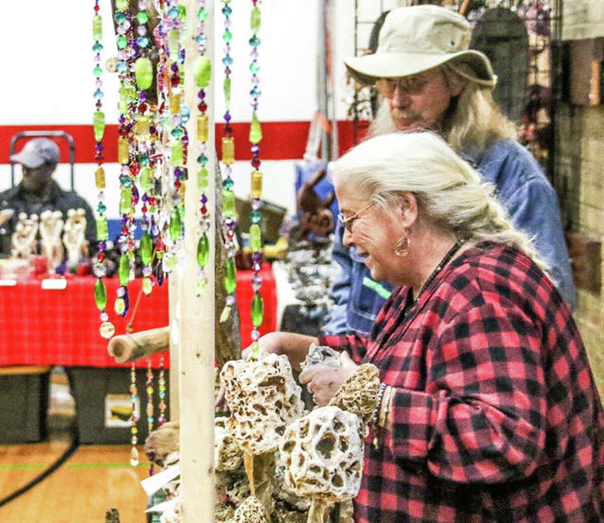 Sherry Kirbach, alongside her husband, Steve, smiles as she adjusts one of her rock mushroom sculptures Saturday at the Green Gift Bazaar. Warm, sunny weather kept crowds flowing through the rows of displays.