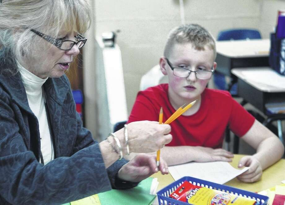Nathan Mortimer of Jacksonville, a student at Washington Elementary School, listens closely Monday as substitute teacher Julie Bruninga explains a worksheet.