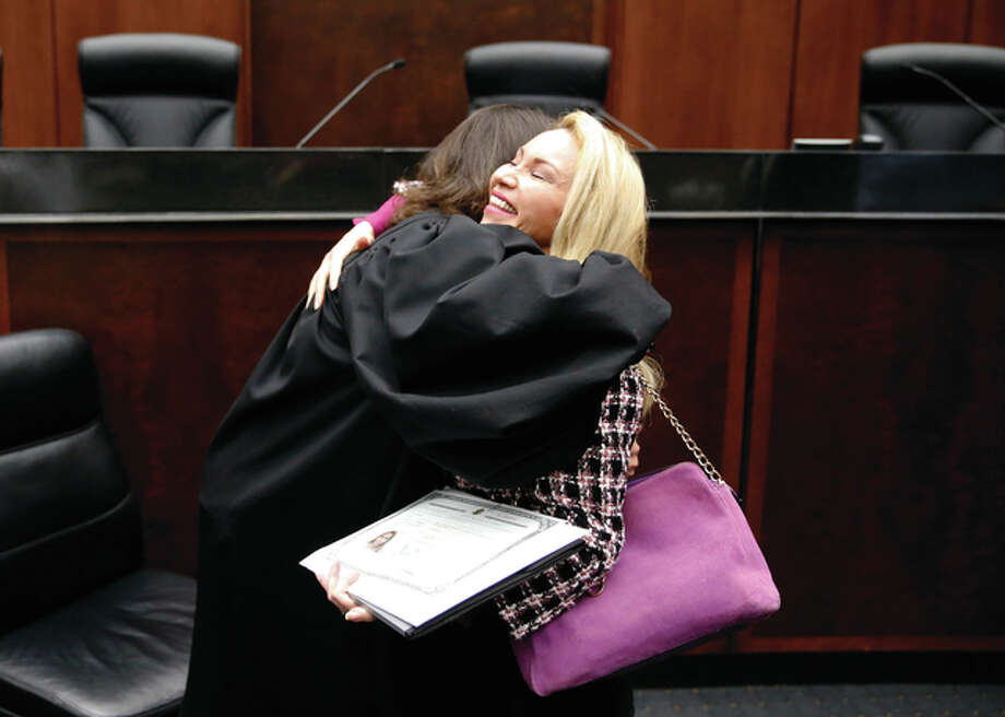 Aseel Jan (right) from Iraq hugs U.S. District Judge Sara Ellis after Jan and 116 others from 37 countries became citizens during a naturalization ceremony Tuesday in Chicago. Photo: Charles Rex Arbogast | AP