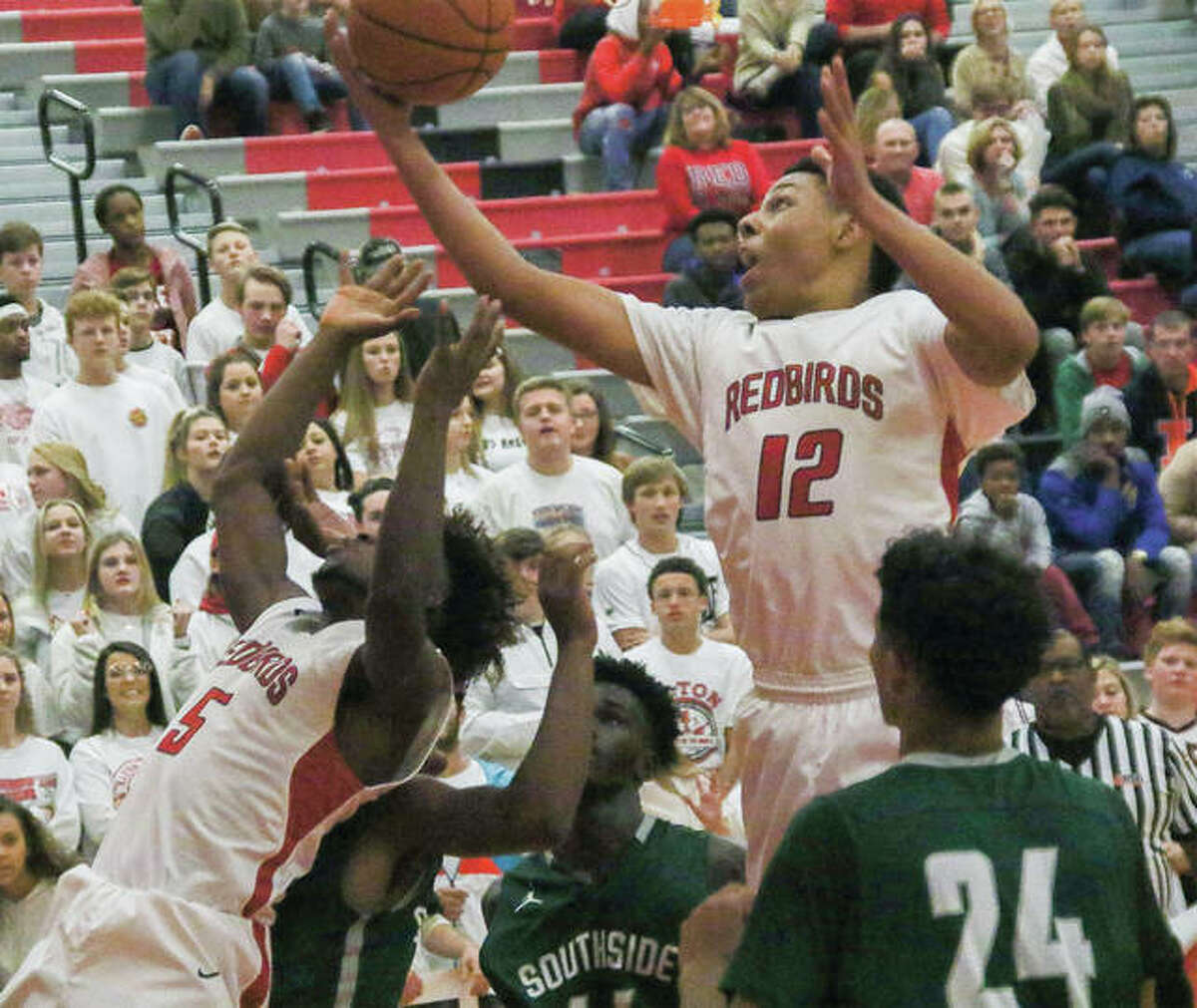 Alton's Josh Rivers (12) comes down with a rebound during the chamopionship game of the Alton Tip-Off Classic on Saturday night at Alton High in Godfrey. Rivers had 11 points in the loss that left the Redbirds with a 3-1 record.
