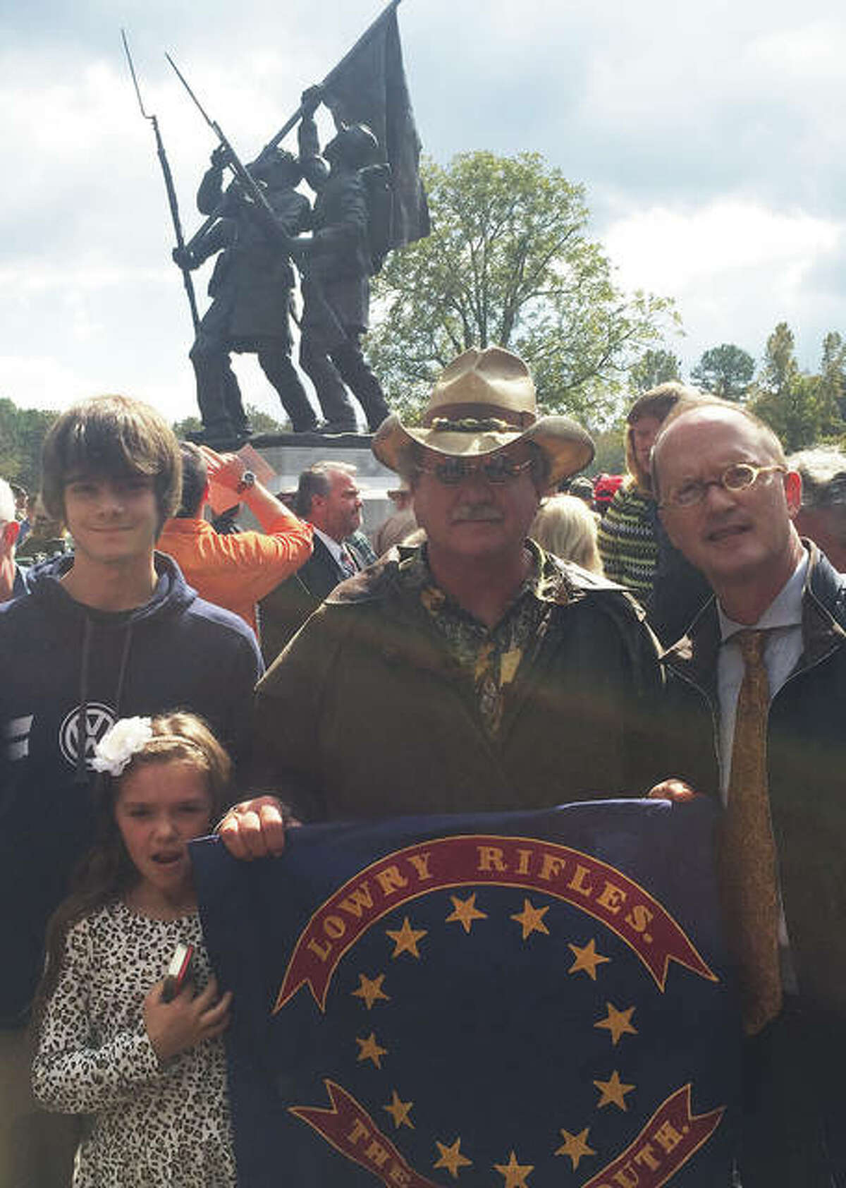 For The Telegraph Justin Ottolini, left, Maria Stanton, and John Stanton, center, at the dedication ceremony in Mississippi for the unveiling of a monument depicting their ancestor at Shiloh in Tennessee. They are posing with their ancestor's flag and with the monument's sculptor.