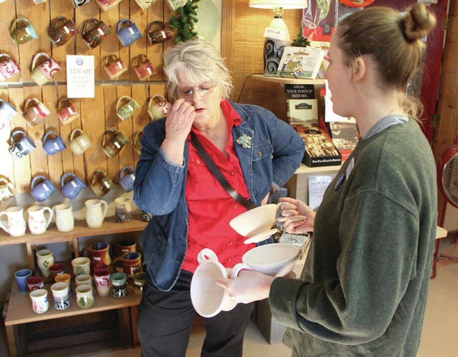 Nancy Heafner, of Godfrey, looks over potential gifts at Mississippi Mud Pottery with the help of co-owner Felicia Breen Saturday. The shop was partiicpating in Small Business Saturday, a promotion aimed at locally-owned stores and restaurants. Photo: Scott Cousins | The Telegraph
