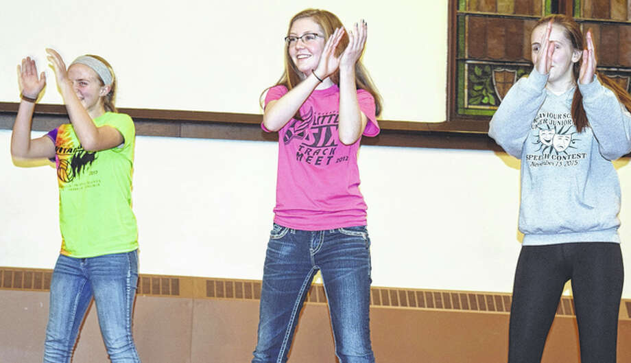 "Ava Schilsky (left), and Anchor Club members Madison Robinson and Ellie Robinson perform the ""Catholic School Dance"" during the club's talent show Wednesday. Photo: Samantha McDaniel-Ogletree 