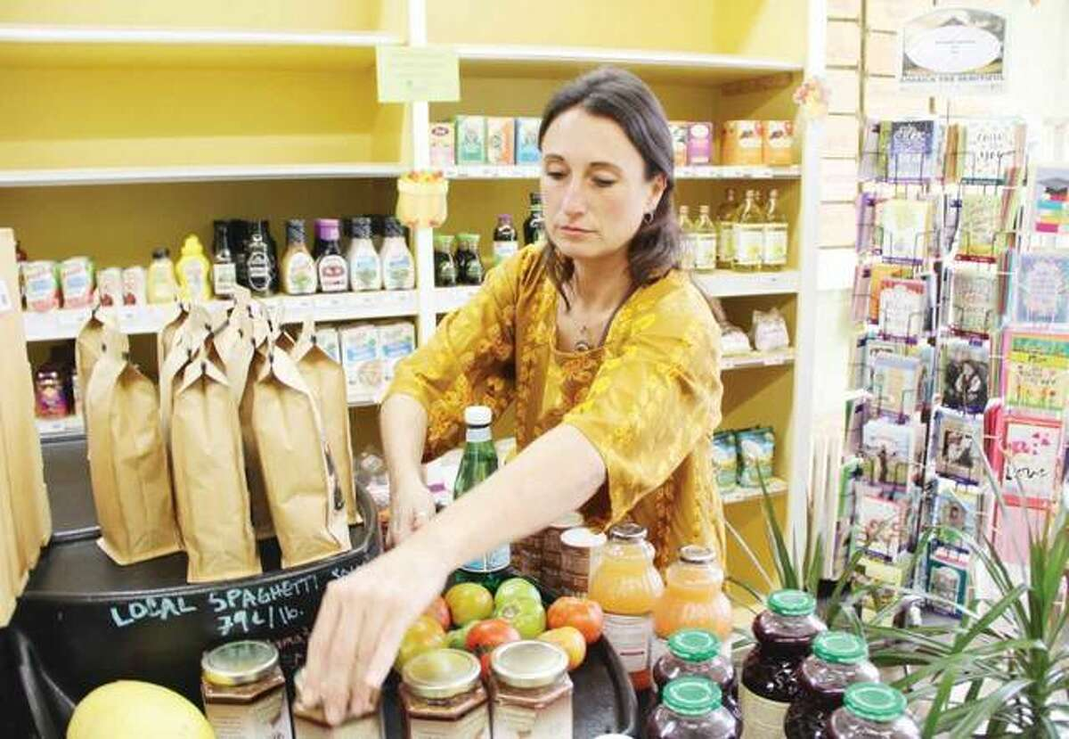 Volunteer Sara McGibany, co-founder of Grassroots Grocery in Alton, arranges some of the merchandise that remains during the ongoing liquidation sale before the co-op closes next month.