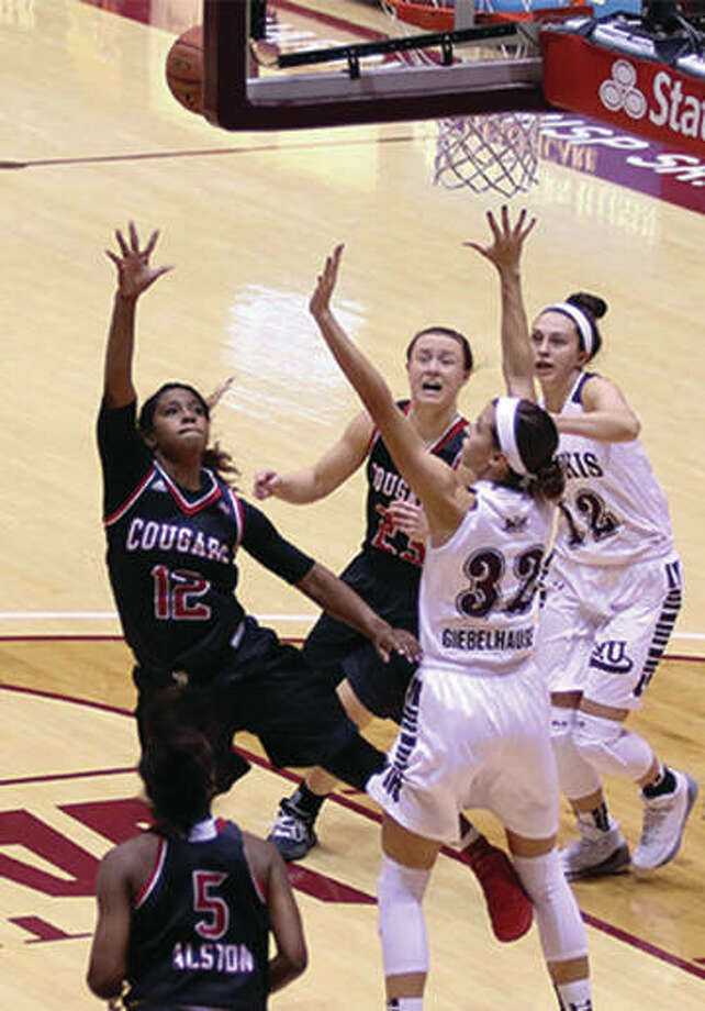 SIUE's Lauren White (12) puts up a shot over SIUC's Kylie Giebelhausen while SIUE's Allie Troeckler (middle, back) and SIUC's Makenzie Silvey watch the play Monday night at SIU Arena. Photo: SIUE Athletics