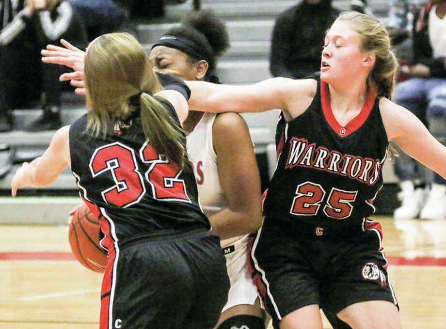 Calhoun's Ashleigh Presley (right) and Sophie Lorton (32) apply pressure in a double-team during the Alton Tip-Off Classic on Nov. 15 in Godfrey. Under a new coach and a new-look roster, the Warriors are 2-2. Photo: Nathan Woodside / For The Telegraph