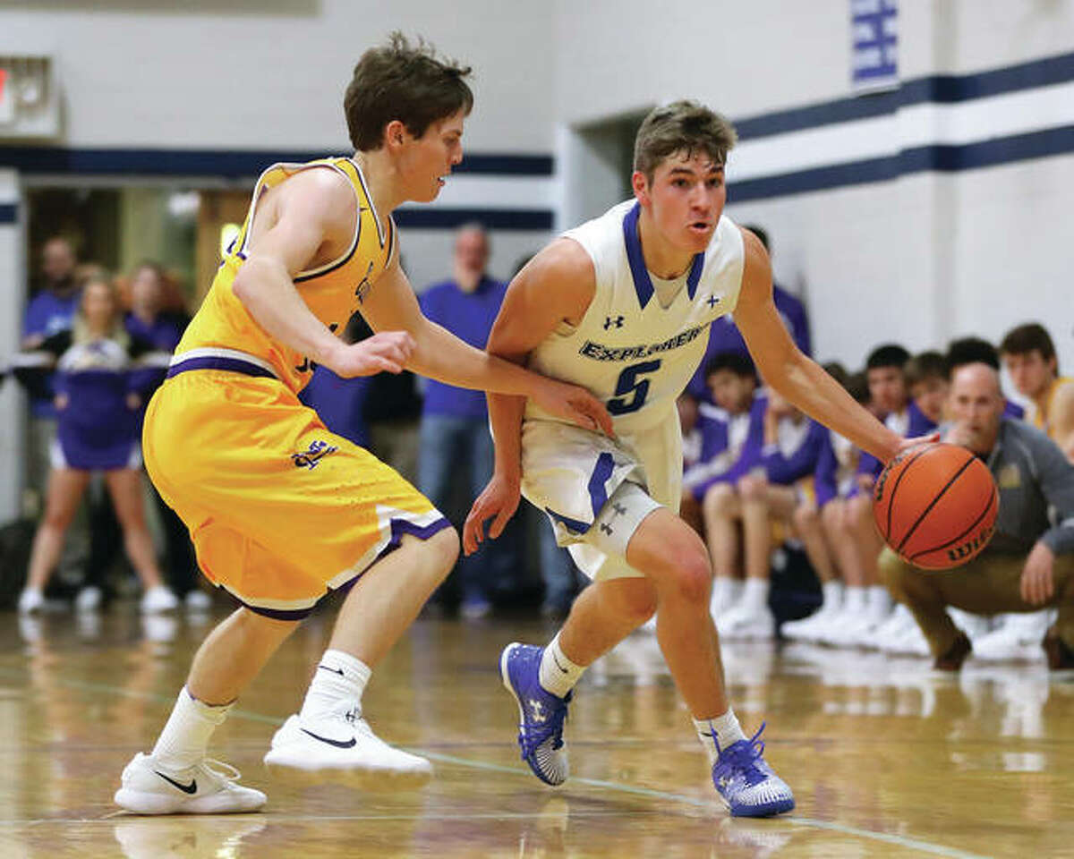 Marquette Catholic's Chris Hartrich (right) handles the ball as he drives past Civic Memorial's Kaleb Denney during Tuesday night's game at Marquette High School in Alton. The Explorers won 58-38.