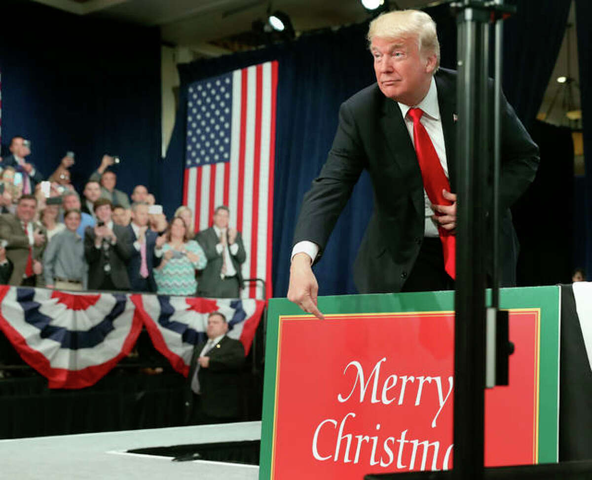 President Donald Trump points to sign that reads Merry Christmas as he arrives to speak about tax reform at the St. Charles Convention Center, Wednesday, Nov. 29, 2017, in St. Charles, Mo.
