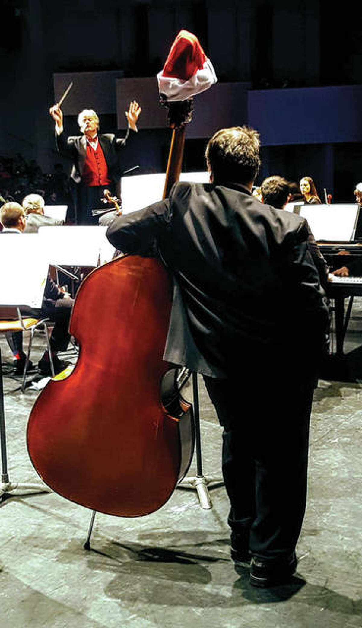 """Maestro Shane Williams, in background, """"cues"""" the orchestra."""