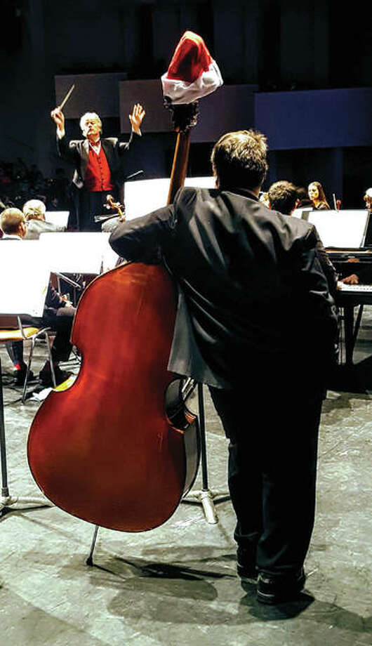 "Maestro Shane Williams, in background, ""cues"" the orchestra. Photo: For The Telegraph"