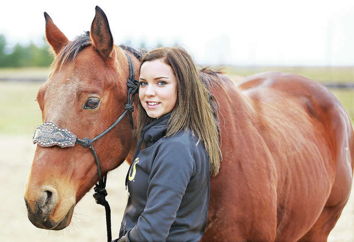 Illini Middle School student Reghan Bollinger, 13, with her horse, Redneck, a 9-year-old male quarter horse, at their home in rural Grafton in Jersey County. Reghan qualified through the National Barrel Horse Association's (NBHA) Illinois State Championships last month, as a 12 year old, for world competition next year. Reghan, who celebrated her 13th birthday Nov. 1, finished both the youth and the open finals with qualifying times at approximately 14 seconds, which topped the youth finals as the fastest time all weekend last month in Gifford, Illinois.