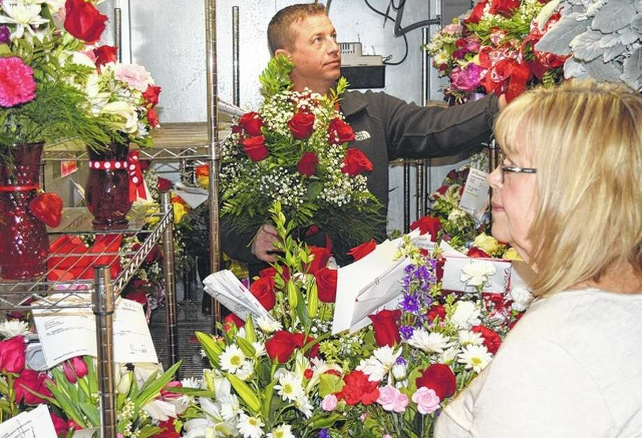 """Mike Chumley helps his mother, JoAnn Chumley, the owner of All Occasions Flowers and Gifts, load orders of flowers Monday for delivery on Valentine's Day. """"We have been really busy,"""" JoAnn Chumley said. """"Love is in the air."""""""