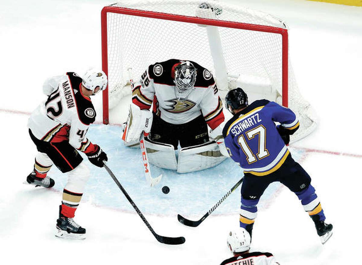 Anaheim Ducks goalie John Gibson stops a shot by the Blues' Jaden Schwartz (17) Wednesday night in St. Louis. At left is the Ducks' Josh Manson.