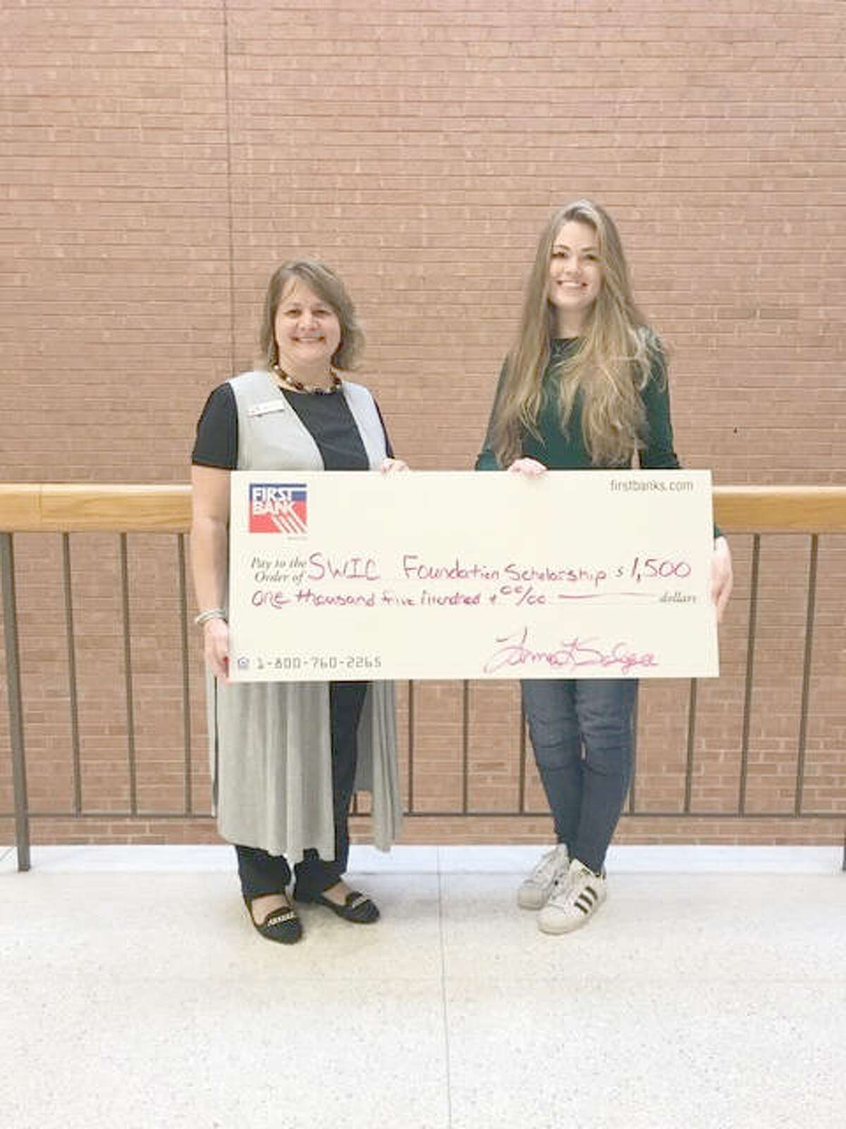 First Bank's Tammy Salger, left, with Skylan Carroll of Highland, one of three scholarship winners from the Metro East.