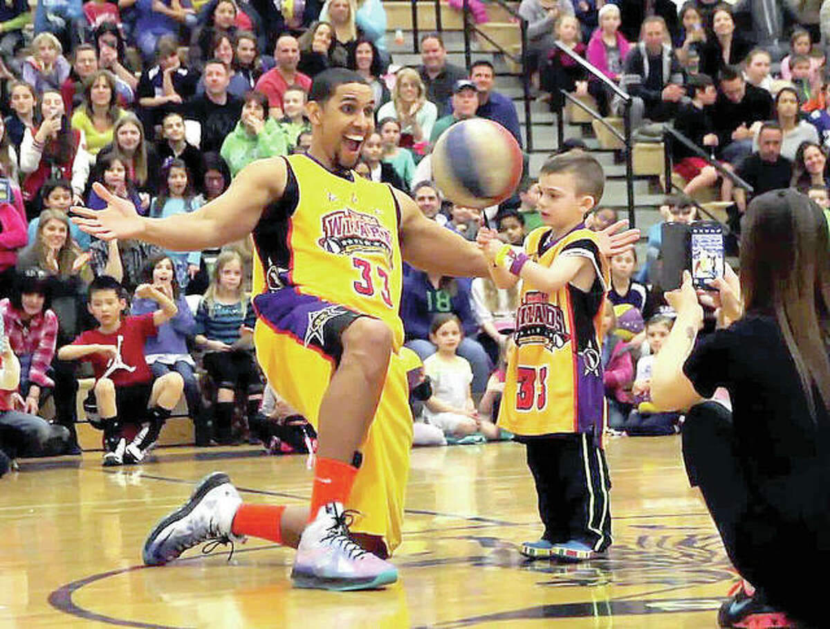 A member of the Harlem Wizards basketball team has fun with a young spectator at a recent benefit game. The Wizards will visit Civic Memorial High at 7 p.m. Dec. 7 for a game versus Bethalto School District teachers and staff. Proceeds will benefit the district's athletic programs