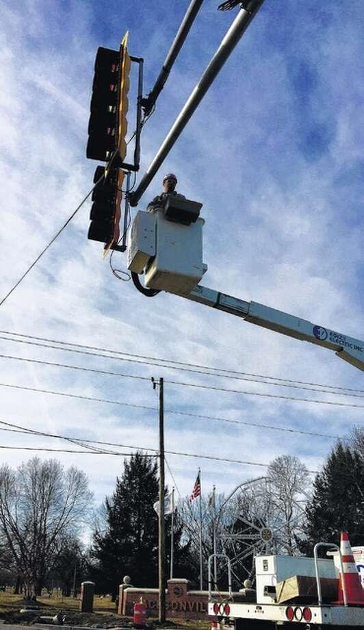 A worker installs a new traffic signal at Main Street and Morton Avenue on Tuesday. Morton Avenue is the focus of a $10.5 million renovation project that includes resurfacing, bridge repairs and sidewalk improvements. It is anticipated the project will be completed in the fall. Photo: Melissa Pantier | For The Journal-Courier