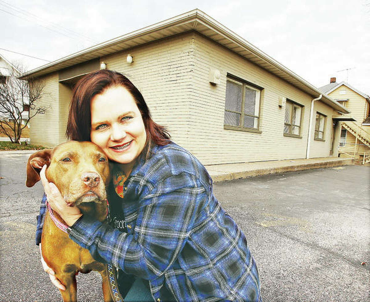 Alicia Jeffreys, owner of the Sham Pooches Grooming animal spa, with one of her canine friends in front of her business' new location at 1735 Main St. in Alton.