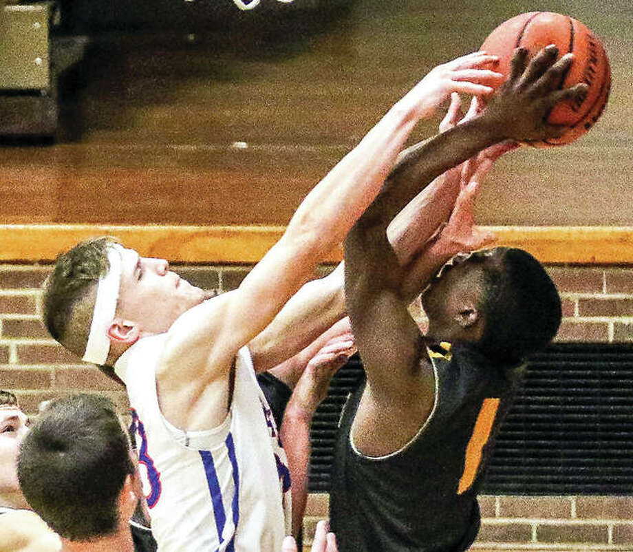 Carlinvile's Josh Hinzman, left, battles Tavion Walker of East Alton-Wood River for a frebound in Friday night's game in Carlinville. Photo: Nathan Woodside | For The Telegraph