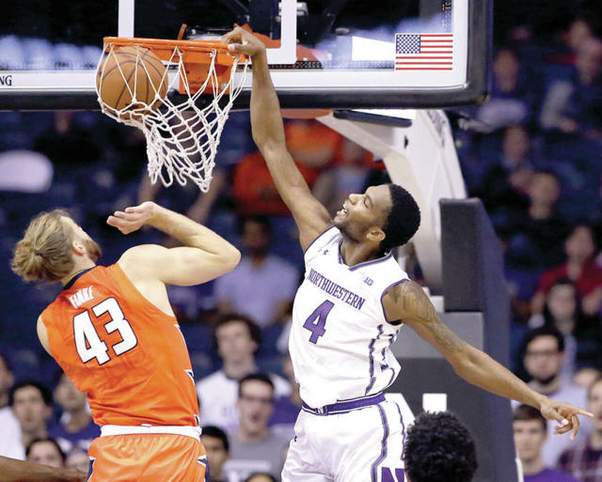 Northwestern forward Vic Law, right, dunks against Illinois forward Michael Finke during the first half of Friday's game in Rosemont. Northwestern outlasted Illinois in overtime.