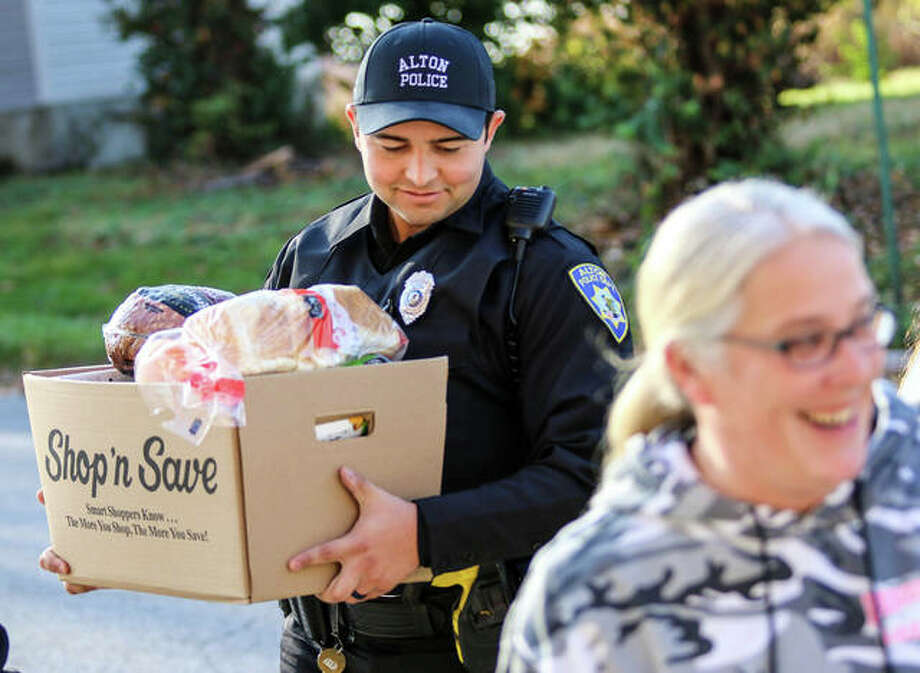 Alton police officer Jacob Potts follows colleague Jennifer Doty into Humboldt Apartments Saturday morning to deliver a food box to a resident there as part of The Police Benevolent and Protective Association of Alton's annual effort to help families in need. Off-duty police officers, their family members and volunteers delivered groceries to 55 local families Saturday. Next Saturday, officers will participate in the annual Shop With A Cop event. The campaigns are thanks to a spring fundraiser that the organization has been holding for 81 years. Photo: Nathan Woodside | For The Telegraph