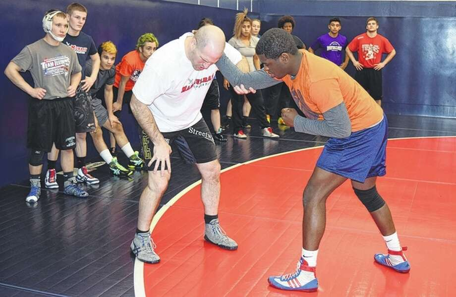 UFC champion Matt Hamill demonstrates wrestling techniques with the help of MacMurray College freshman Ron Evans on Thursday. Hamill worked with the college's wrestling team, as well as the school's American Sign Language students.