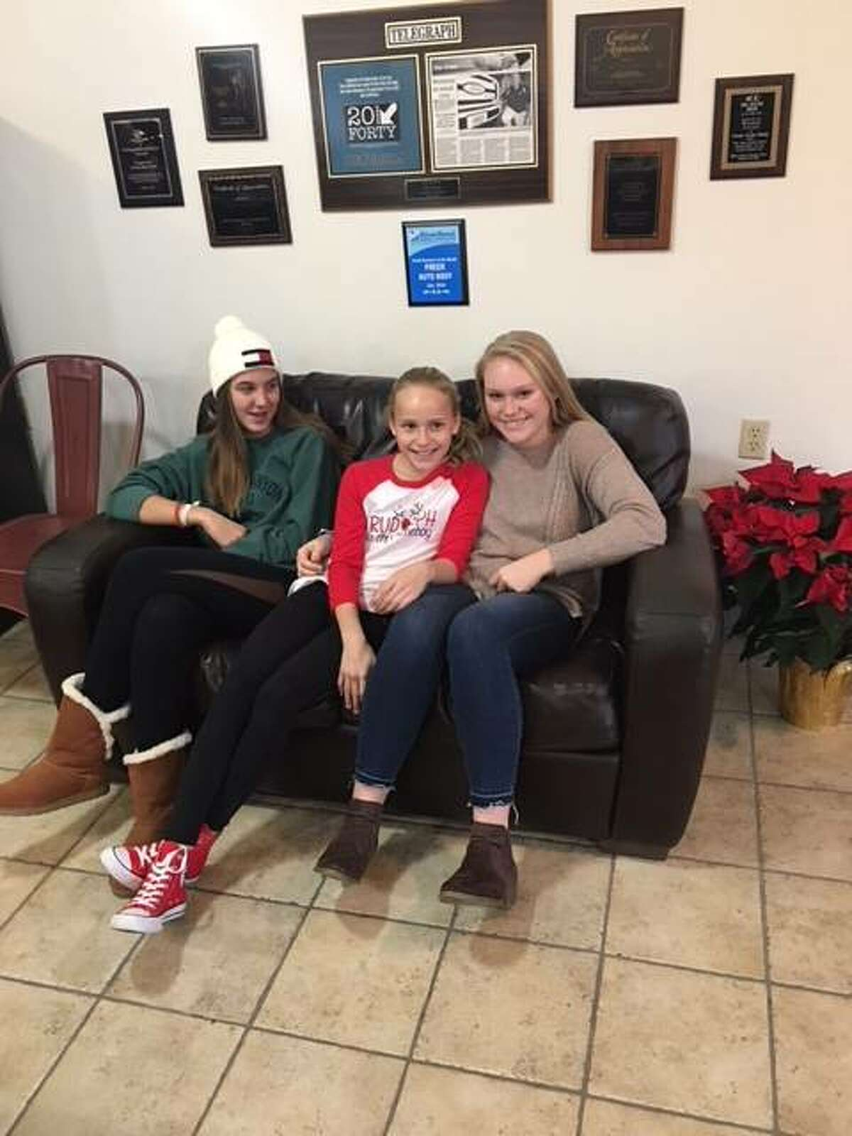 A young volunteer and friend, Riley Clancyput, left, with the Freer sisters, Lily Freer, center, and Taylor Freer, at Freer Auto Body's Community Christmas fundraiser, Cookies and Cocoa, last Thursday held at the Freer family business in Godfrey.